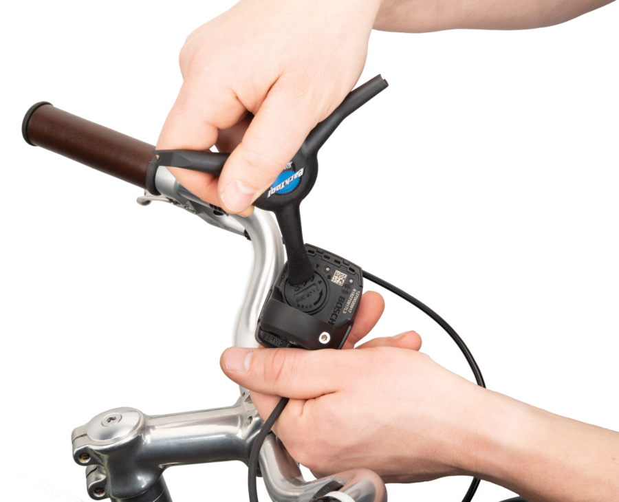 The Park Tool Bicycle Electronic Shift Tool removing a coin cell battery cover, enlarged