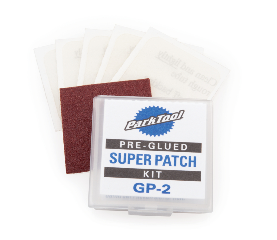 Pre-Glued Super Patch Kit contents (6 patches and small sandpaper) displayed behind packaging, enlarged