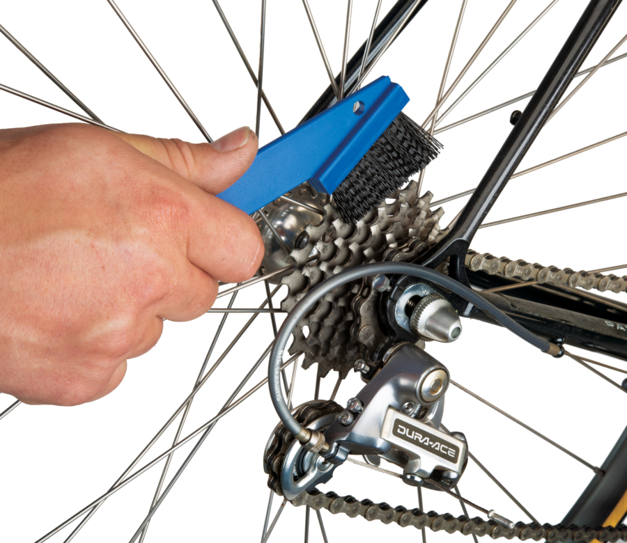 Park Tool GSC-1 GearClean™ Brush held against rear cogs brushing away grime and cleaning, enlarged