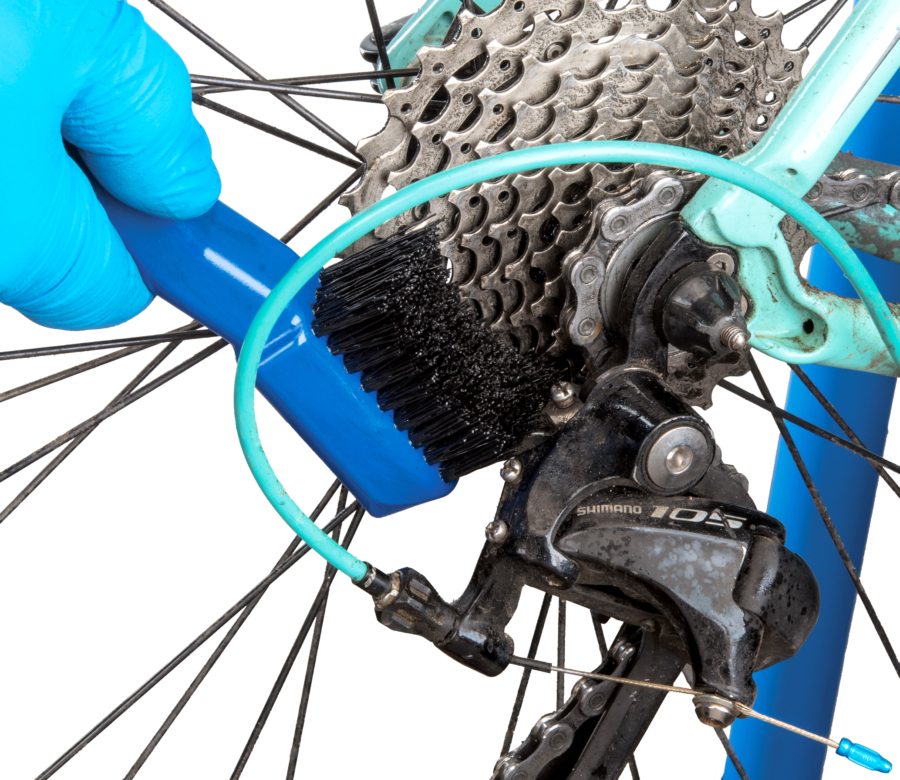 The Park Tool GSC-4 Bicycle Cassette Cleaning Brush cleaning cassette cogs, enlarged