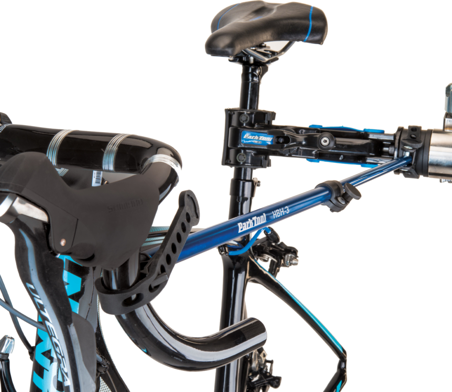 The Park Tool HBH-3 Extendable Handlebar Holder holding drop handlebars on bike in repair stand, enlarged