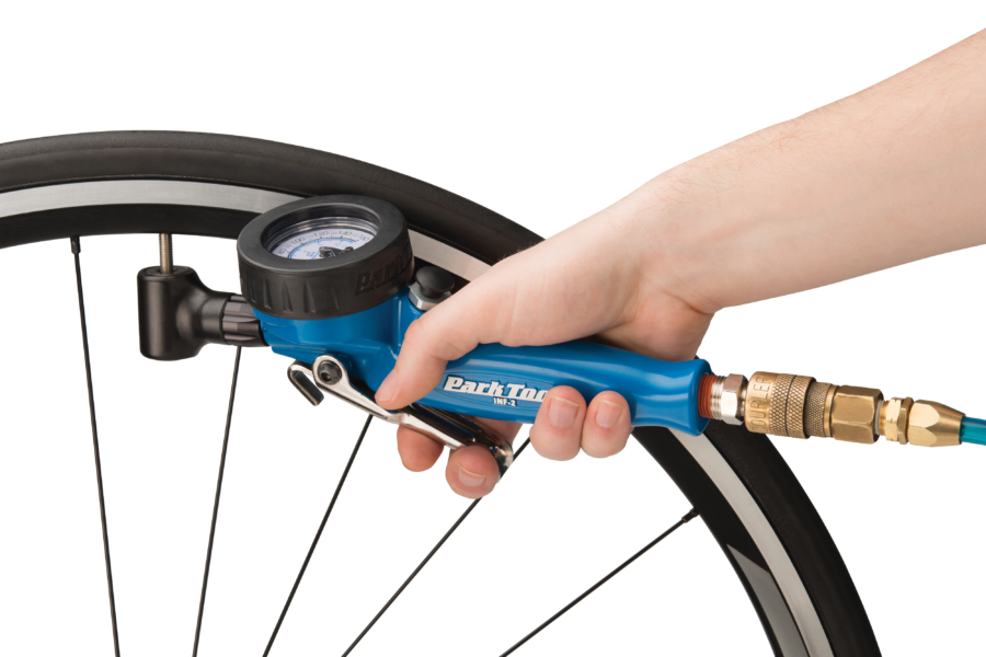 The Park Tool INF-2 Shop Inflator inflating road tire with Presta valve, enlarged