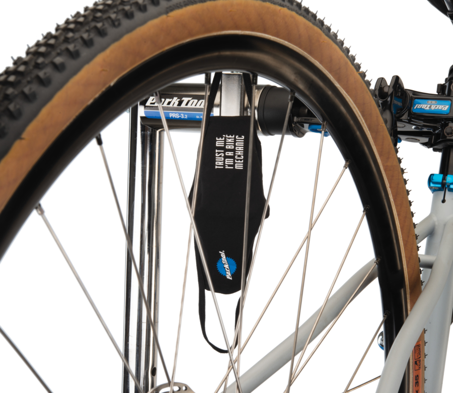 Park Tool MSK-2 Face Mask hanging from a PRS-3.2-2 with bicycle wheel in front, enlarged