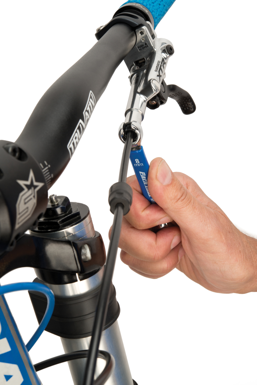 The Park Tool MWF-1 Metric Flare Wrench loosening Shimano® compression fitting at the lever, enlarged