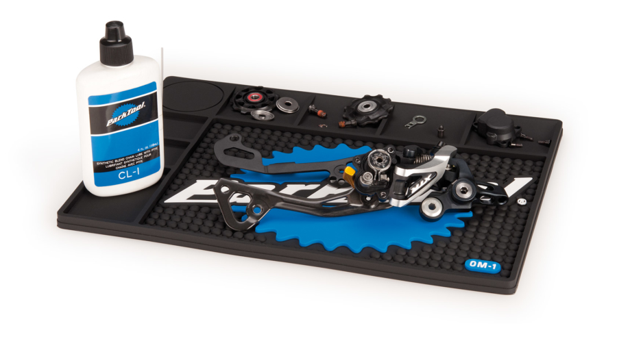 The Park Tool OM-1 Benchtop Overhaul Mat with tools and parts displayed on top, enlarged