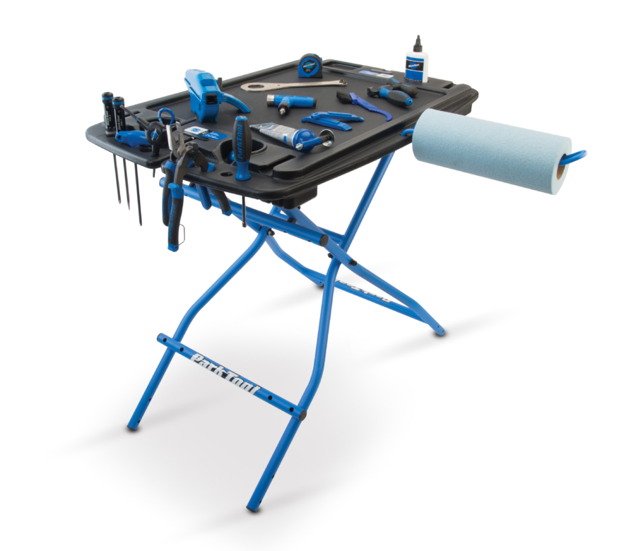 The Park Tool PB-1 Portable Workbench with tools displayed on top and the PTH-1 Paper Towel Holder attached, enlarged