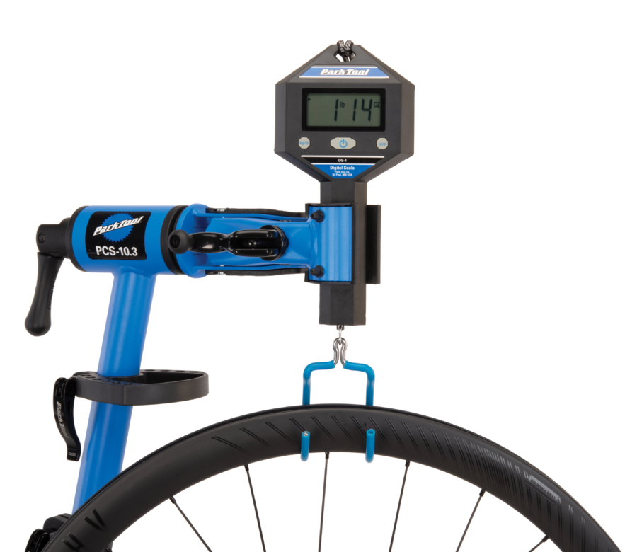 The Park Tool PCS-10.3 Deluxe Home Mechanic Repair Stand holding a DS-1 digital scale to weigh a road wheel, enlarged