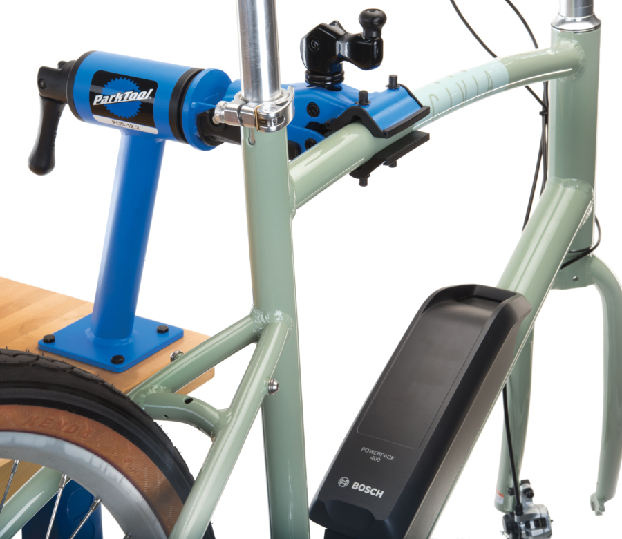 Park Tool PCS-12.2 Home Mechanic Bench Mount Repair Stand mounted to a maple workbench holding a green e-bike, enlarged