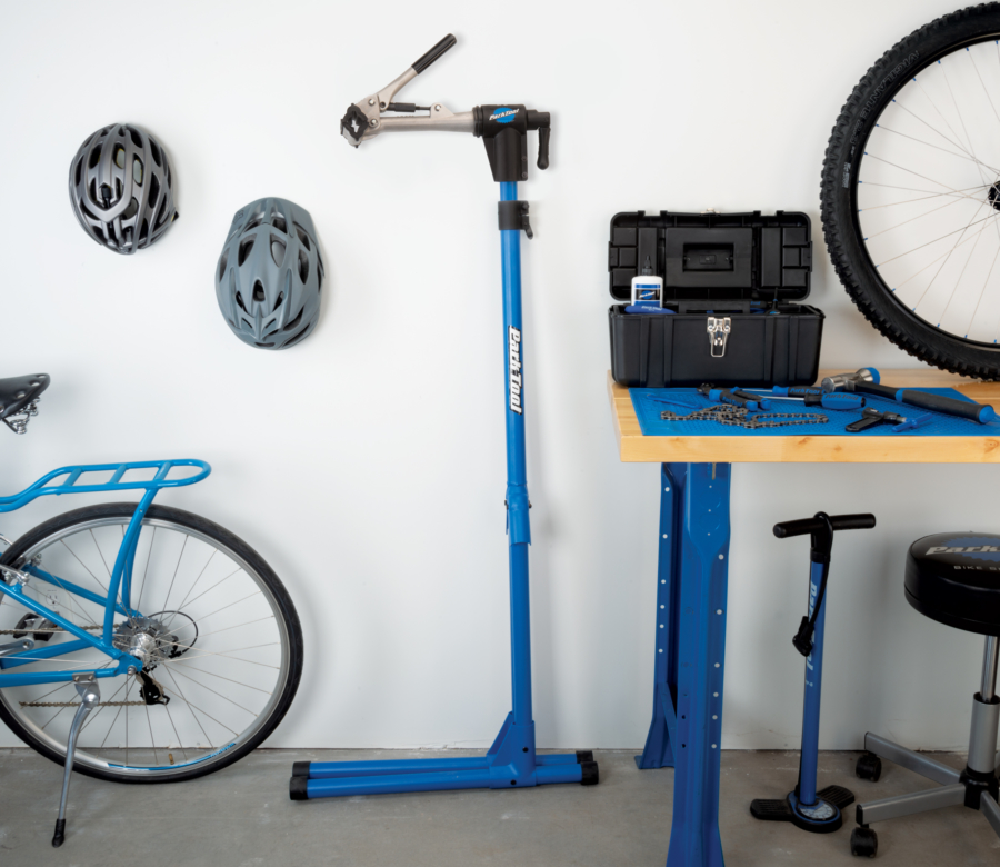 The Park Tool PCS-4-1 Deluxe Home Mechanic Repair Stand folded up, leaning against wall next to workbench, enlarged