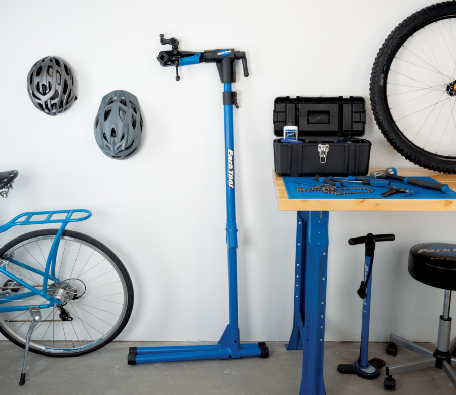 The Park Tool PCS-4-2 Deluxe Home Mechanic Repair Stand folded up, leaning against wall next to workbench, enlarged