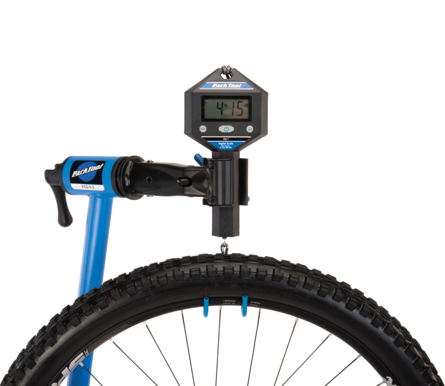 The Park Tool PCS-9.3 Home Mechanic Repair Stand holding a DS-1 digital scale to weigh a MTB wheel, enlarged
