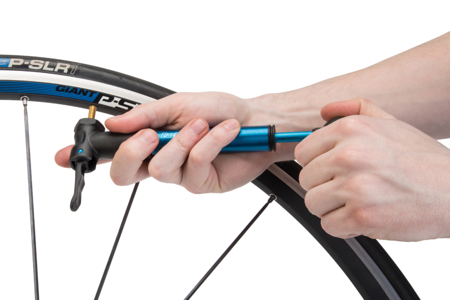 The Park Tool PMP-3.2 Micro Pump in blue being used on bike tire, enlarged