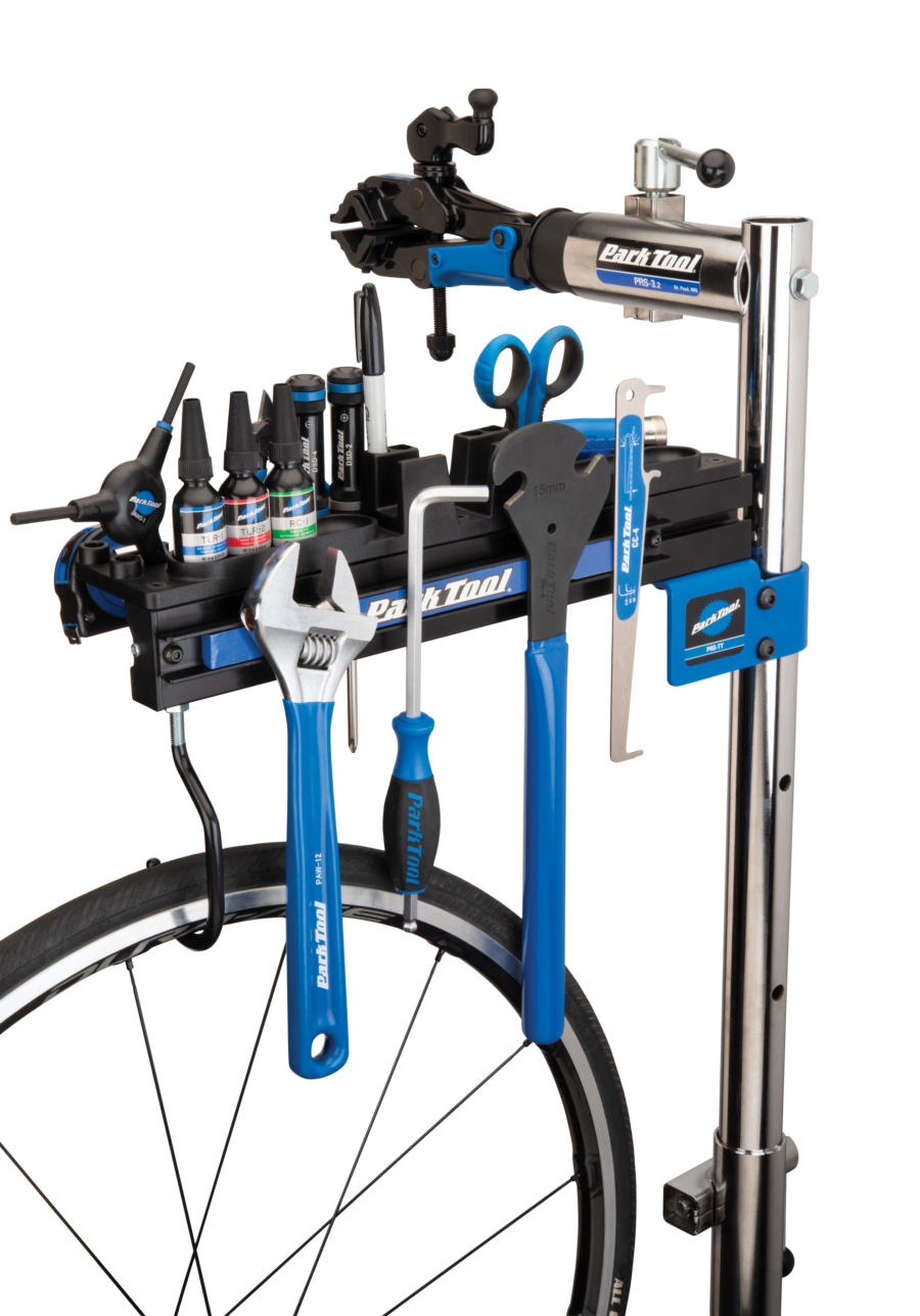 Park Tool PRS-TT Deluxe Tool and Work Tray on top of a Park Tool repair stand filled with tools, enlarged