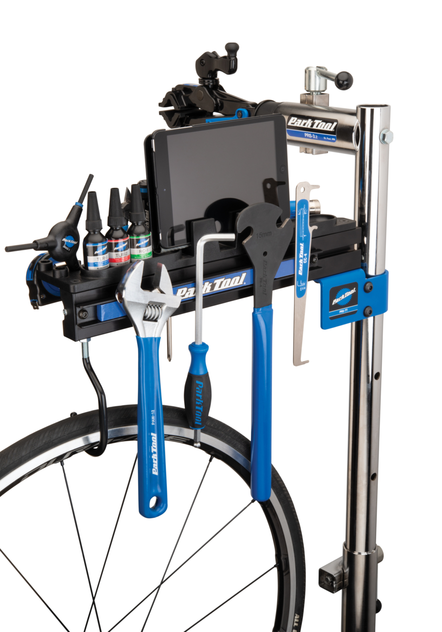 Park Tool PRS-TT Deluxe Tool and Work Tray on top of a Park Tool repair stand filled with tools and an Ipad, enlarged