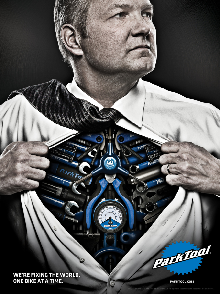 Park Tool advertisement man in super man pose exposing chest of bike tools, enlarged