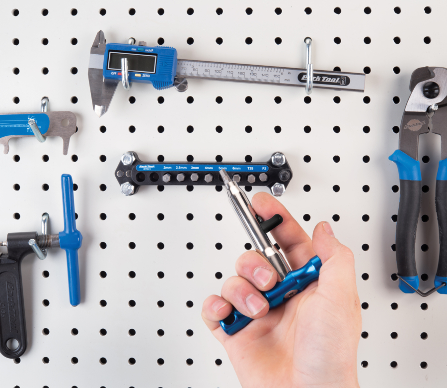 The Park Tool QTH-1 Quick Change Bit Driver Set handle returning a bit to holder mounted on pegboard, enlarged