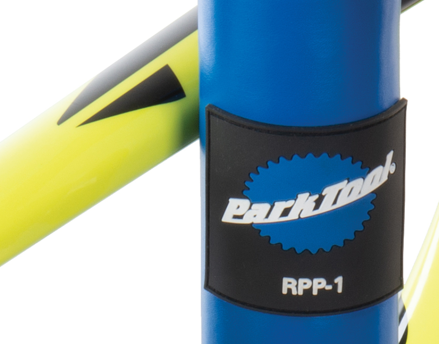 Close-up of Park Tool RPP-1 Repair Stand Post Protector TPE logo badge with yellow bike leaned against it, enlarged