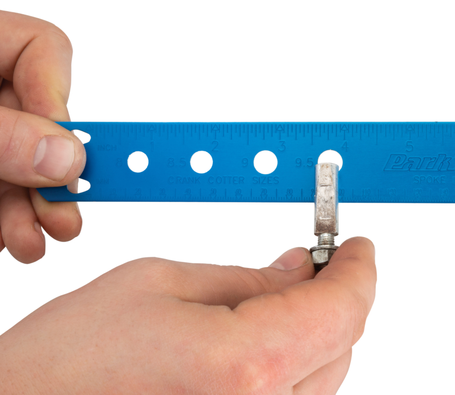 The Park Tool SBC-1 Spoke, Bearing and Cotter Gauge being used to measure a crank cotter pin, enlarged