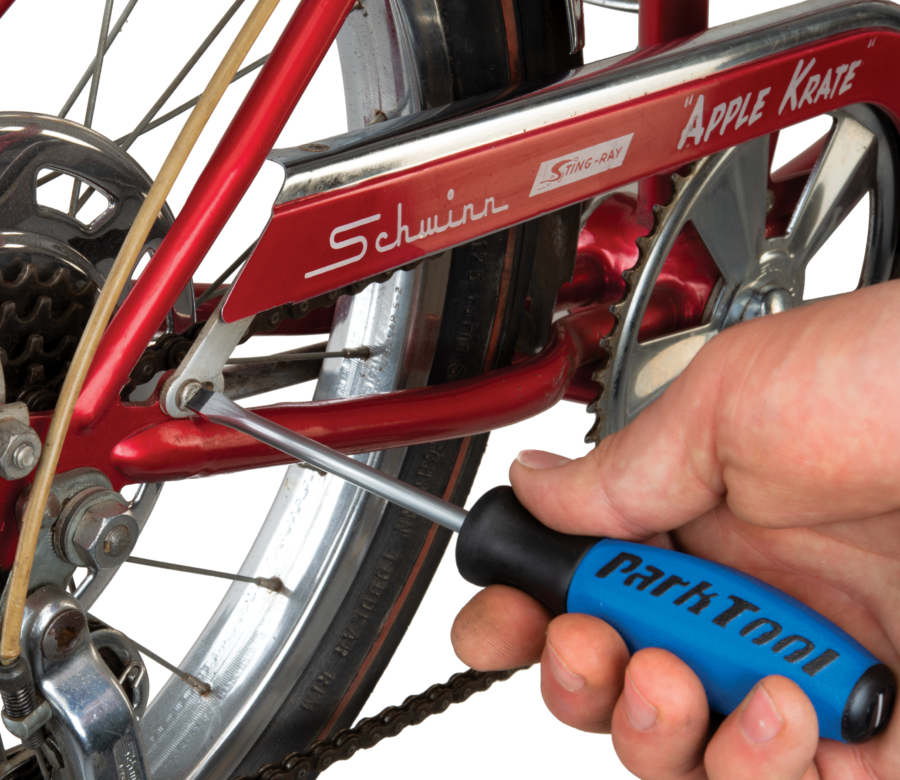 Park Tool SD-6 6mm Flat Blade Screwdriver loosening screw on chain guard of red bicycle, enlarged