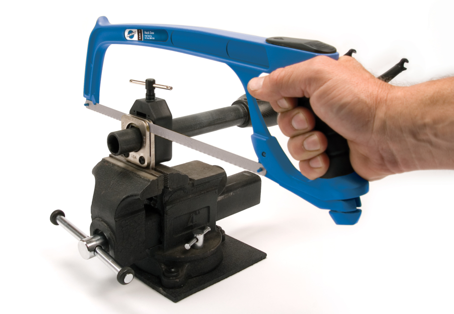 The Park Tool SG-6 Threadless Saw Guide in vise, holding fork tube while hacksaw cuts, enlarged