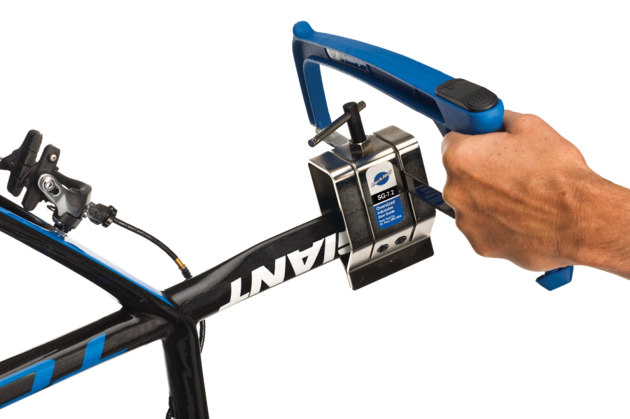 The Park Tool SG-7.2 Oversized Adjustable Saw Guide clamped onto aero seat post while hacksaw cuts, enlarged