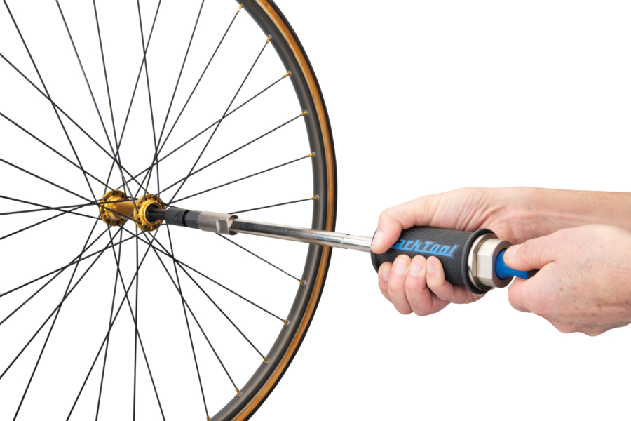The Park Tool SHX-1 Slide Hammer Extractor installed in hub bearing, driver hitting end of the slide hammer, enlarged