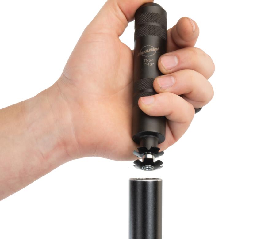 The Park Tool TNS-1 Threadless Nut Setter preparing to install star-fangled nut into fork steerer tube, enlarged