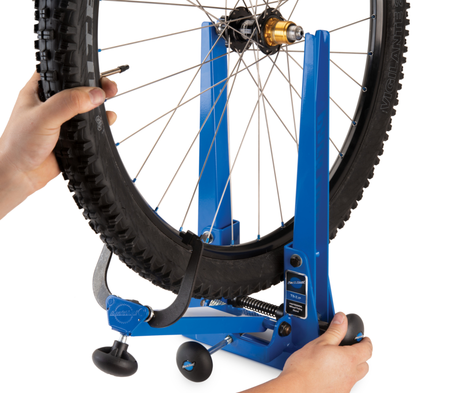 Black 29er rim and tire being inserted into TS-2.2 Powder Coated Professional Wheel Truing Stand, enlarged