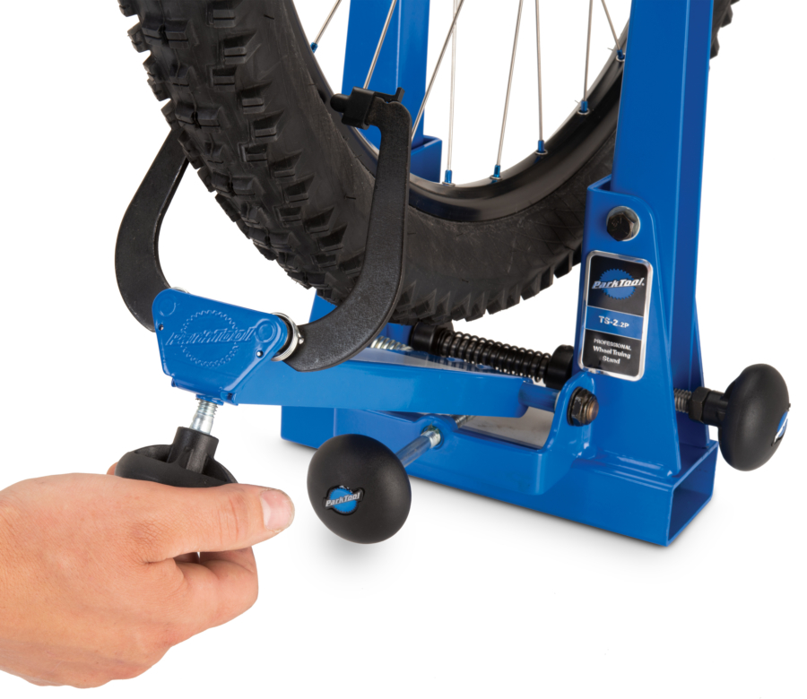 TS-2.2P Powder Coated Professional Wheel Truing Stand calipers being adjusted closer to wheel in stand, enlarged