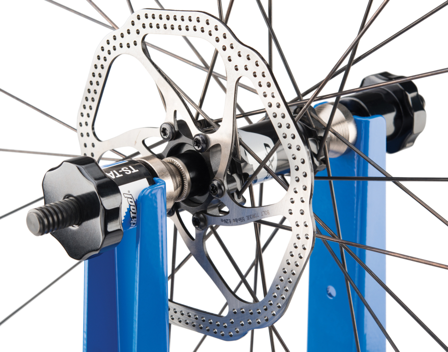 Close-up of Park Tool TS-TA Thru Axle Adaptor holding a bike wheel in TS-2.2P Professional Wheel Truing Stand, enlarged