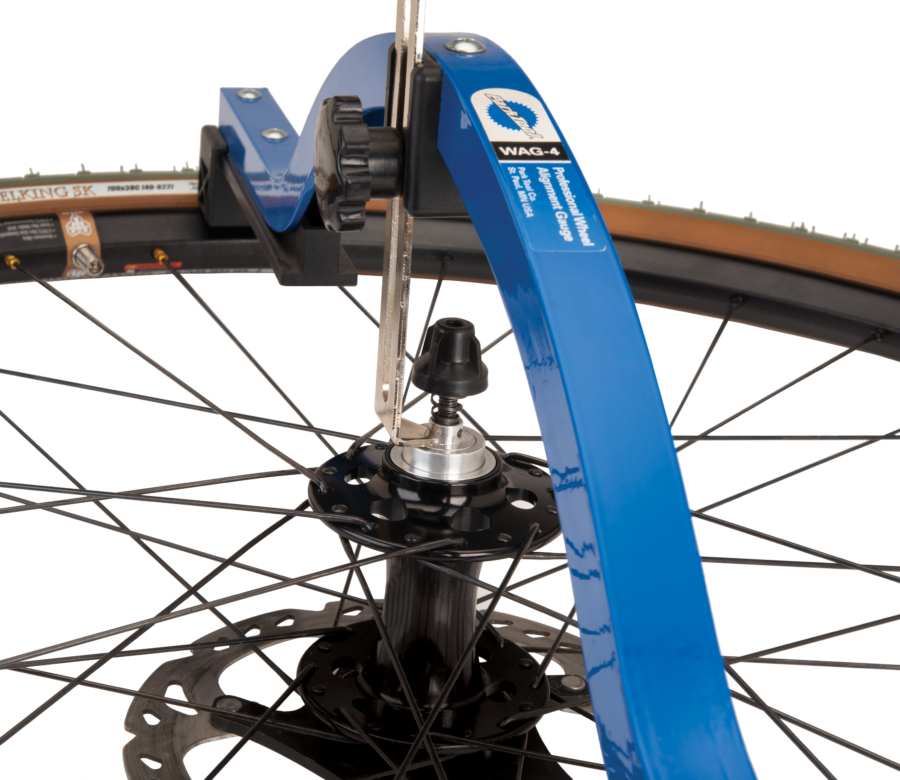The Park Tool WAG-4 Professional Wheel Alignment Gauge indicator resting on outer edge of front axle, enlarged