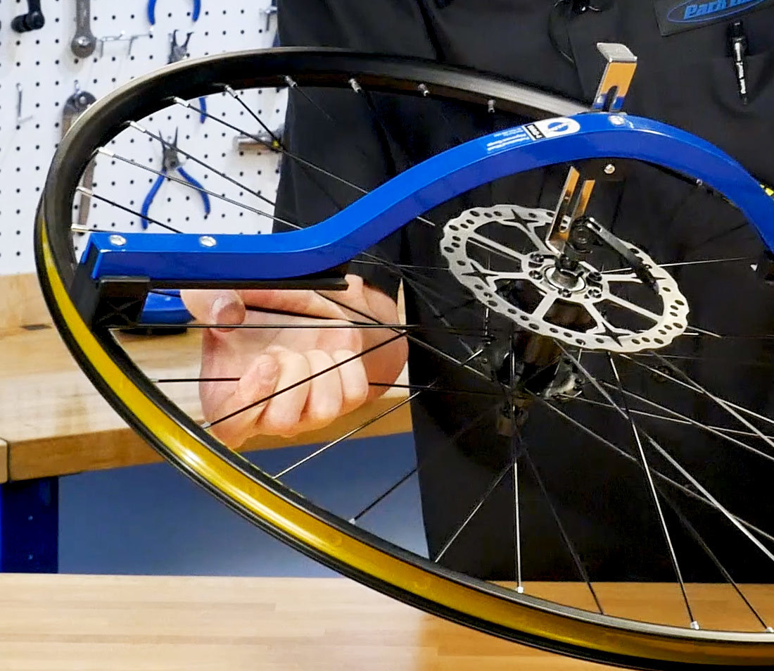 By squeezing a pair of spokes on the underside of this wheel...