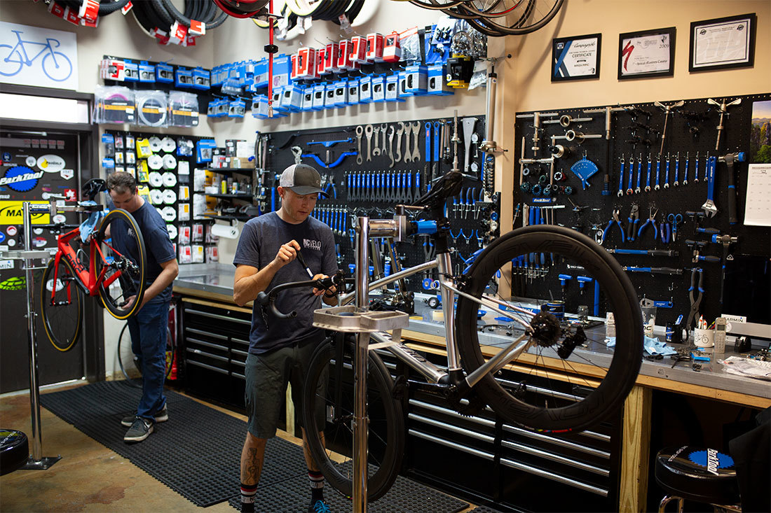 Typical service center in a bike shop with two bicycle mechanics working on bikes