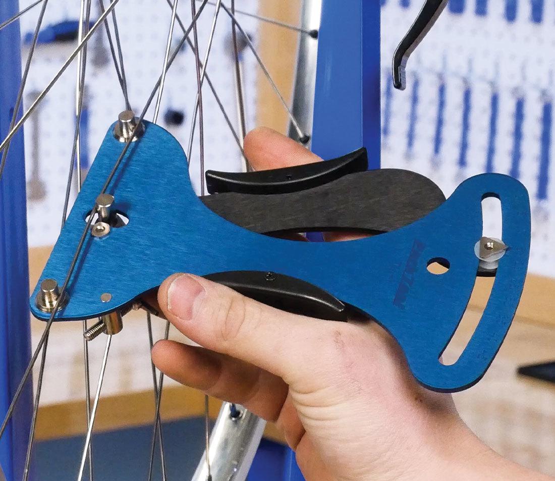 A bicycle spoke being meausured by a spoke tensiometer