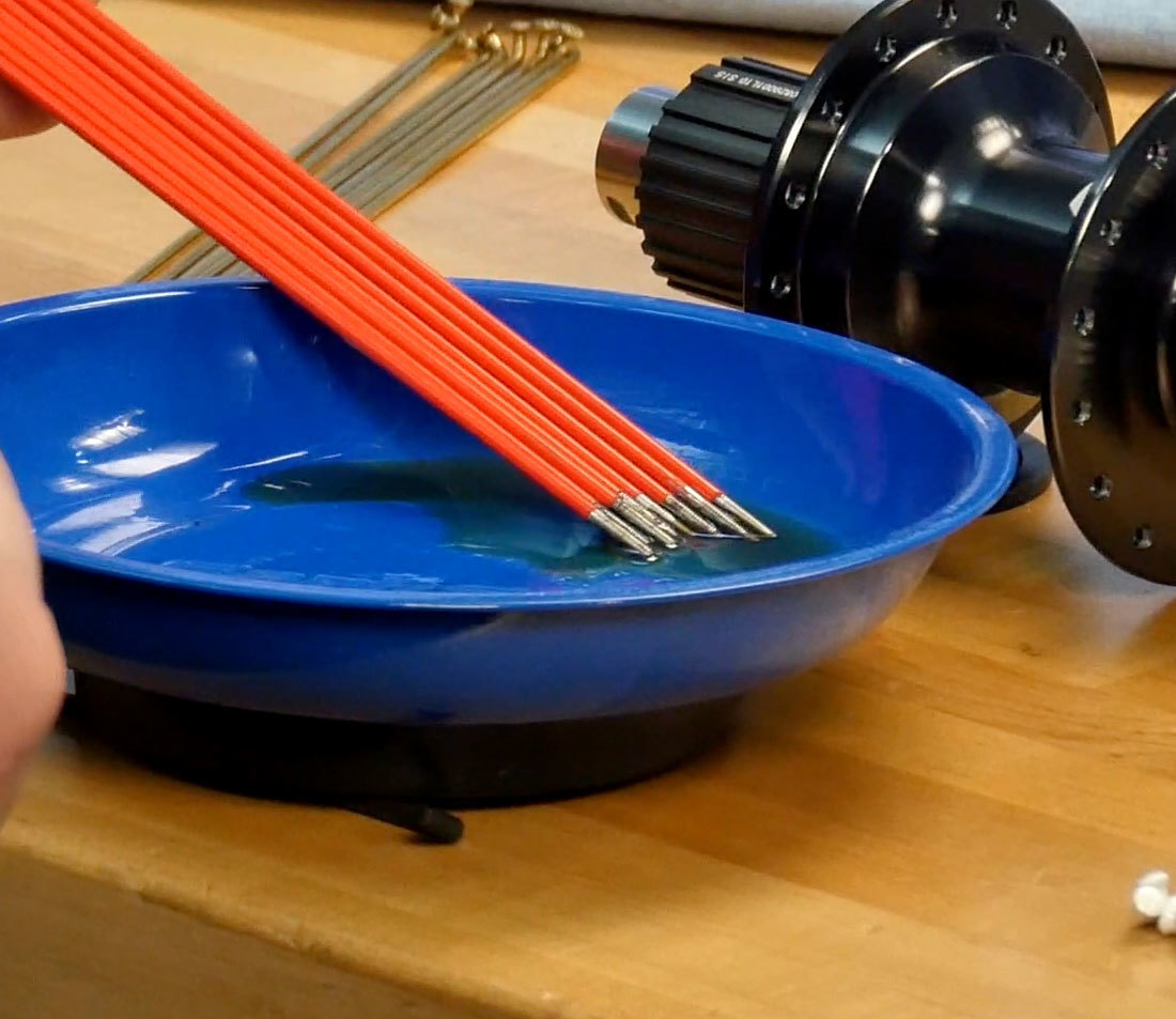 Threaded spoke ends resting in magnetic bowl with lubricant