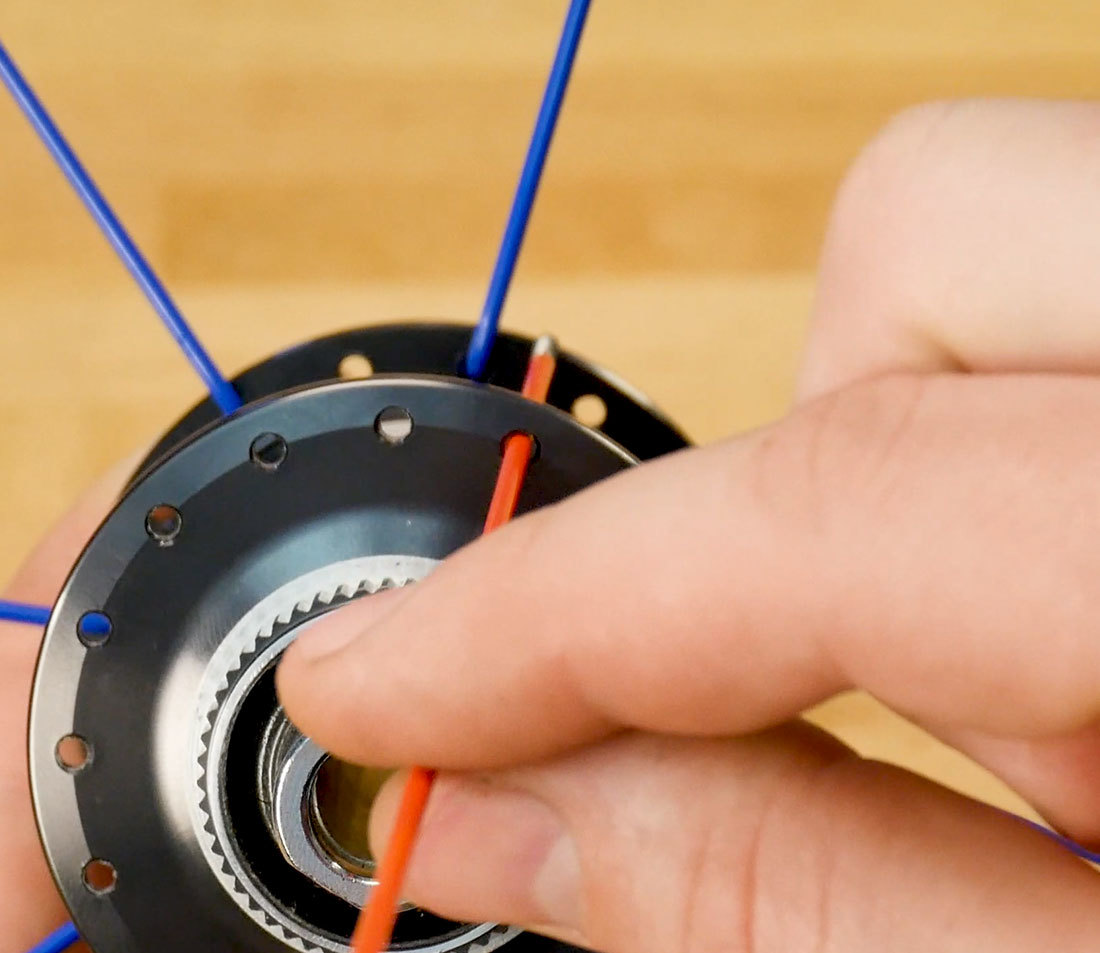 View of hub from one side with one spoke inserted to show slight offset from spokes on opposite side