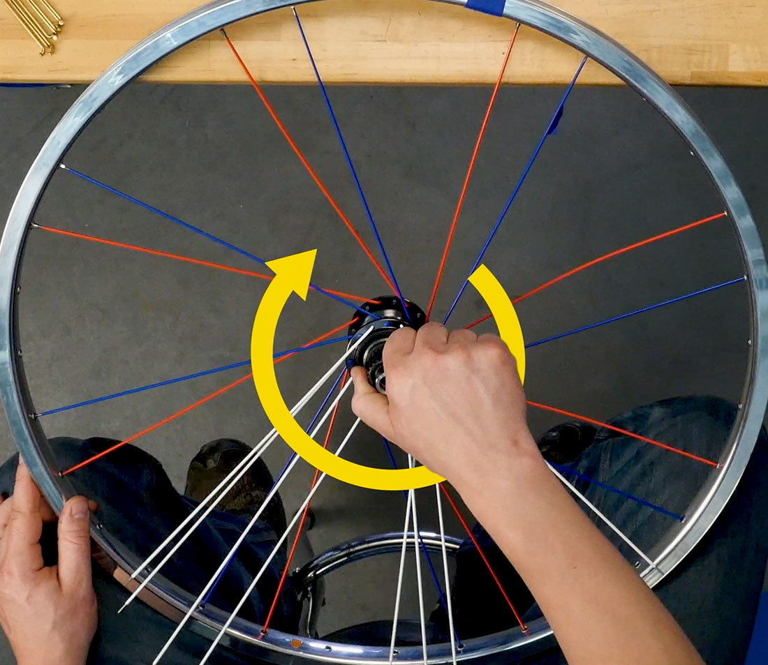 Hub of partially assembled wheel being twisted in clockwise motion