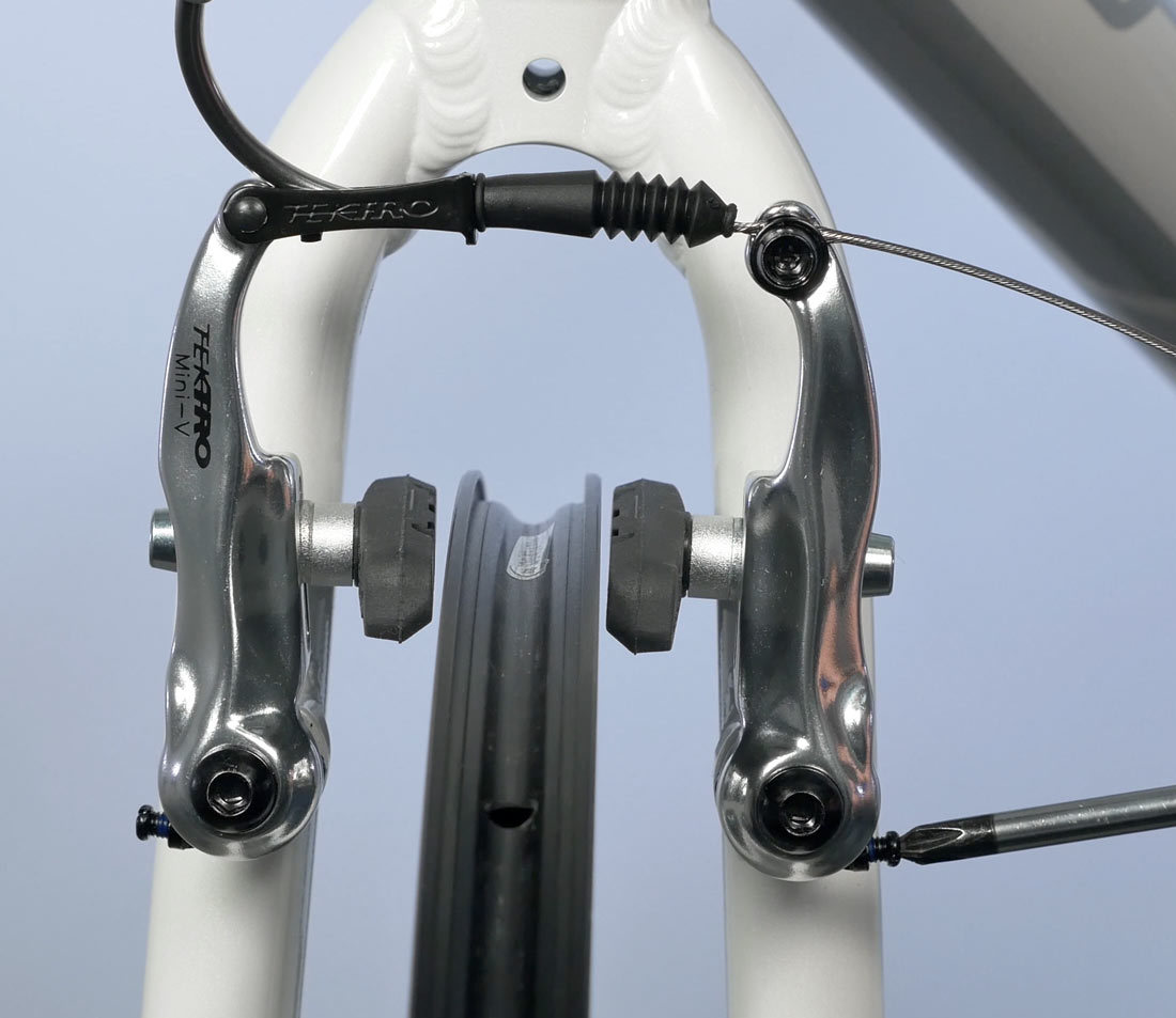 Use centering screw to move arms and center pads to rim